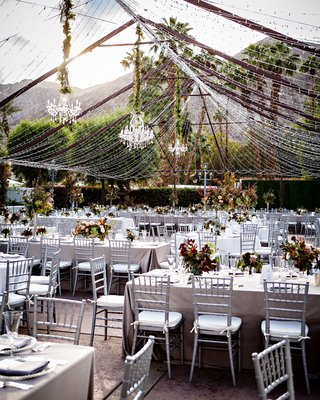wedding-reception-outdoor-silver-chairs-fall-color-centerpieces-chandeliers-tent-made-out-of-lights
