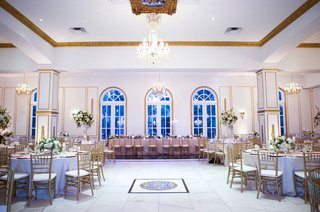 room-shot-of-wedding-reception-in-chateau-ballroom-chandelier-pink-long-table-and-round-tables-dance