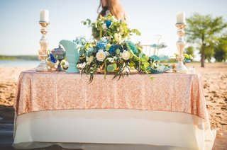 mermaid-beach-inspired-tablescape-with-sequin-tablecloth-greenery-blue-flowers-white-florals