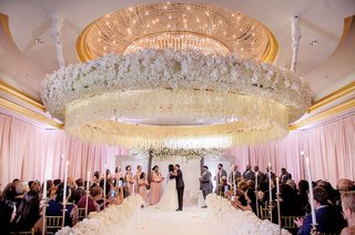wedding-ceremony-large-white-flower-circle-over-dance-floor-kiss-newlyweds-ballroom-ceremony-candles