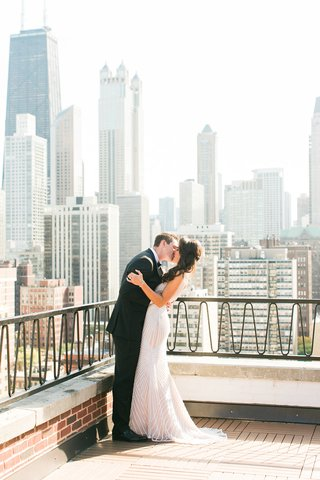 bride-and-groom-kiss-on-chicago-balcony-with-skyscrapers-and-skyline-in-background