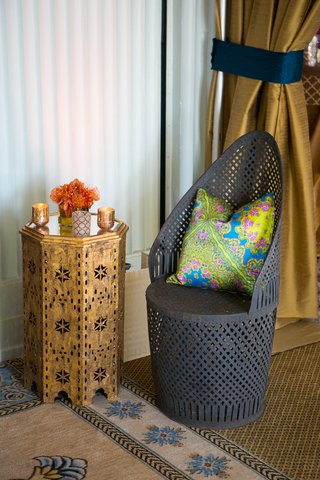 metalwork-chair-with-green-blue-yellow-patterned-throw-pillow-at-moroccan-style-engagement-party