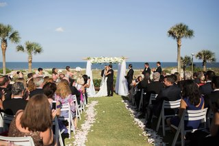 oceanfront-wedding-on-lawn-bridal-party-applauds-first-kiss-between-bride-and-groom