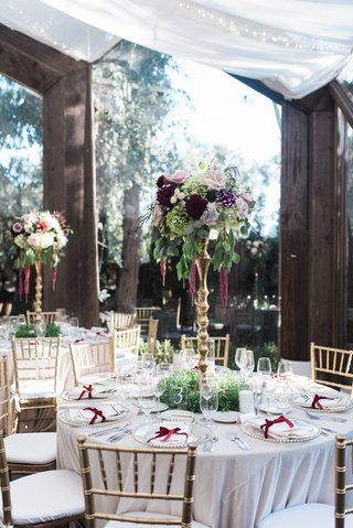 tall-centerpiece-on-gold-stand-with-fall-flowers-and-greenery