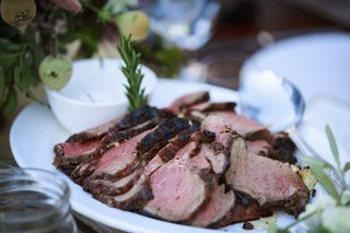 ranch-wedding-table-with-platter-of-grilled-beef-tenderloin-sprig-of-rosemary