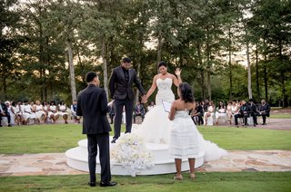 bride-and-groom-on-raised-platform-outdoor-courtyard-private-estate-wedding-ceremony-white-flowers