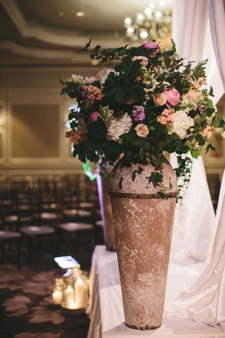 large-vase-with-flowers-and-greenery-at-wedding-ceremony