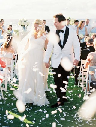 bride-and-groom-walking-up-aisle-white-tuxedo-jacket-ocean-wedding-white-confetti-grass-lawn