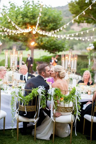 bride-and-groom-sitting-in-gold-chairs-foliage-ribbon-kiss-head-table-candelabra-strung-up-lights