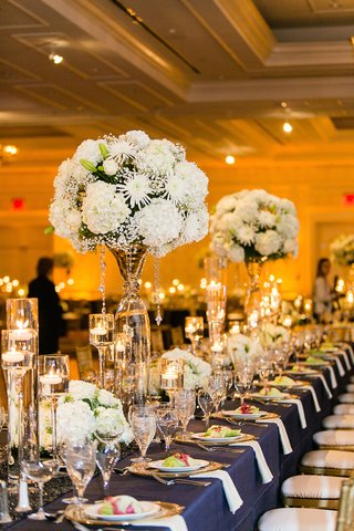 navy-blue-tablescape-at-wedding-with-tall-white-flower-arrangements
