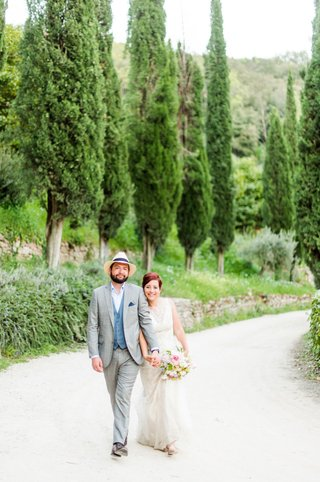bride-in-wedding-dress-with-bouquet-groom-in-casual-suit-with-hat-italy-destination-wedding-umbria