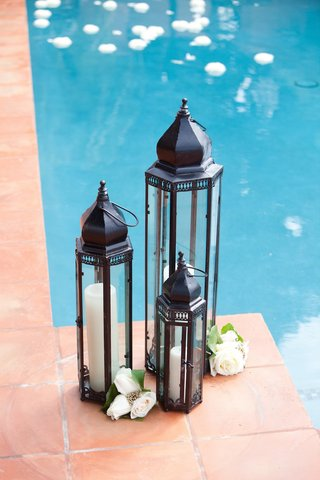black-panel-lantern-filled-with-tall-candles-next-to-pool