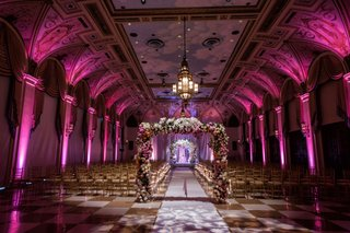 wedding-ceremony-in-ballroom-at-the-breakers-with-flower-arch-pink-lighting-and-checker-floor