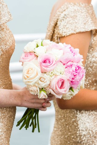bridesmaid-in-gold-holds-bouquet-with-pink-and-ivories-roses-pink-peonies