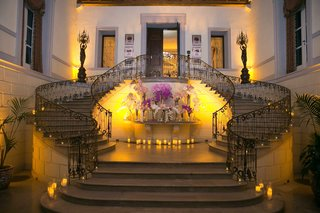 grand-staircase-at-oheka-castle-with-pink-and-purple-flower-arrangements-in-center-yellow-lighting