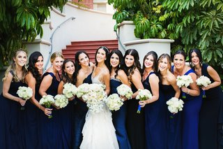 bride-with-bridesmaids-in-mismatched-bright-blue-wedding-dresses-white-rose-bouquets