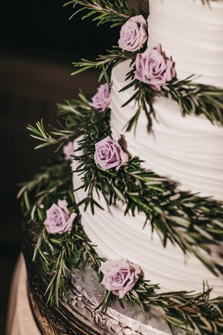 close-up-of-white-wedding-cake-with-tiers-decorated-with-rosemary-sprigs-and-mini-lavender-roses