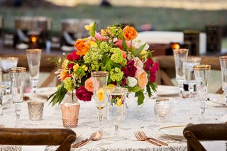rose-gold-flatware-and-glassware-rims-low-centerpiece-orange-green-red-pink-yellow-flowers-wood