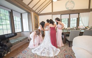bridesmaids-in-morilee-and-maid-of-honor-help-bride-into-her-wedding-dress