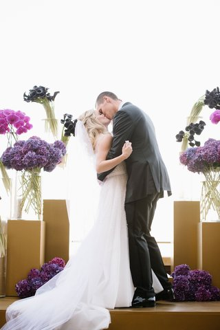 wedding-ceremony-kiss-bride-and-groom-gold-stage-altar-with-purple-flowers-hydrangea-calla-lily