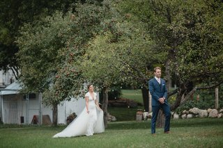 wedding-photo-first-look-bride-in-lace-dress-overskirt-groom-in-navy-suit-pink-tie-waiting-by-tree