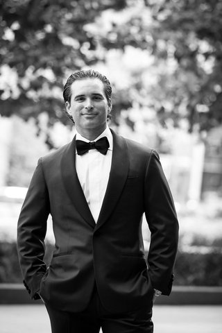 black-and-white-photo-groom-in-tuxedo-and-bow-tie-with-slicked-back-hair-in-new-york-city