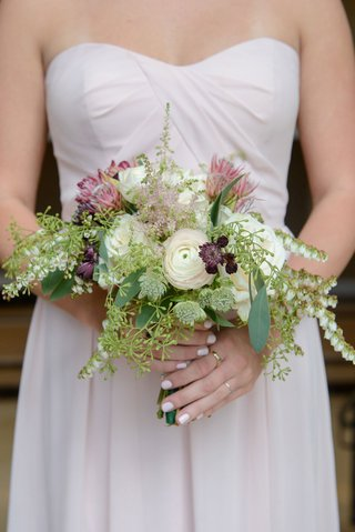 bridesmaid-with-draped-dress-bouquet-of-protea-ranunculus-and-greenery-fall-bouquet-ideas
