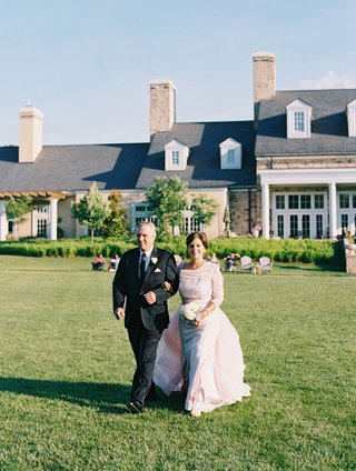 wedding-ceremony-lawn-green-grass-countryside-resort-mother-of-bride-in-pink-dress-with-father