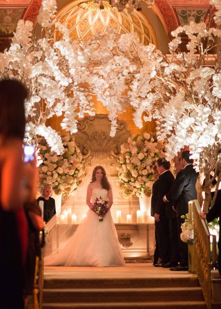 bride-holding-purple-white-bouquet-down-aisle-with-orchid-branches-overhead