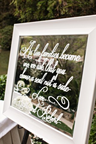 a-ceremony-seating-sign-made-from-a-mirror-with-white-writing