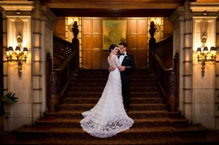 bride-in-lace-v-neck-carolina-herrera-groom-in-ralph-lauren-hug-on-staircase