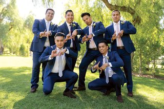 groomsmen-in-navy-suits-and-different-color-ties-doing-la-symbol-with-their-hands