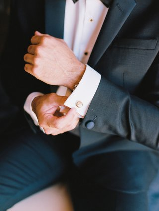 groom-in-tuxedo-with-bow-tie-putting-on-cufflinks-cuff-links-round-gold