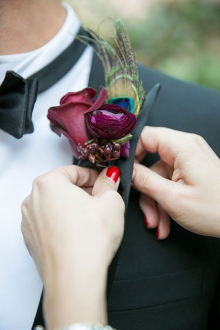 woman-with-red-nail-polish-putting-on-boutonniere-lapel-for-groom-peacock-feather-and-purple-flowers