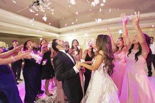 wedding-guests-tossing-flower-petals-during-first-dance-hotel-ballroom