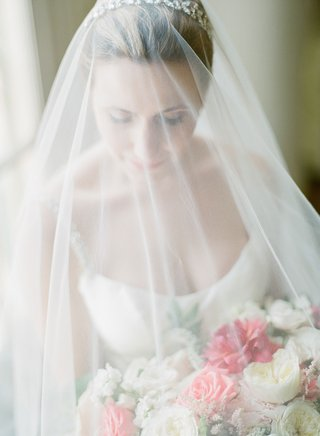 bride-in-strap-wedding-dress-scoop-neck-under-veil-with-headband-pink-and-white-bouquet-roses