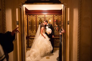 bride-and-groom-kiss-in-elevator-at-the-plaza-hotel-in-new-york-city-after-wedding