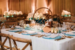 ocean-inspired-wedding-reception-with-wood-bud-vases-succulents-blue-charger-gold-flatware