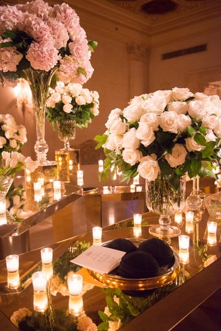 yarmulkes-kippahs-sitting-on-top-of-reflective-table-at-jewish-ceremony-with-candles-and-flowers