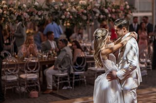 wedding-reception-first-dance-bride-in-boho-wedding-dress-groom-in-ivory-suit-guests-at-head-tabl