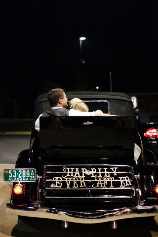 bride-and-groom-leaving-the-reception-in-a-black-classic-convertible