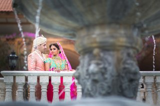 indian-american-bride-in-pink-and-turquoise-lehenga-groom-in-traditional-outfit