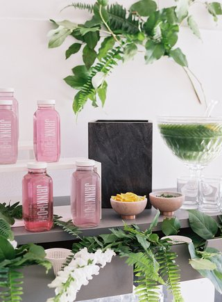 cold-pressed-juice-jrink-pink-drink-in-bottles-punch-in-crystal-tray-on-bar-cart-ferns-greenery