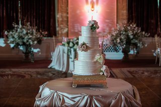 four-tiered-wedding-cake-with-fresh-flowers-and-buttercream-frosting