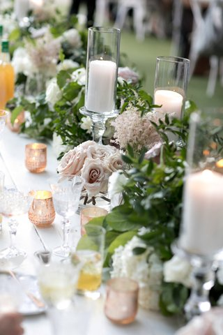 wedding-reception-head-table-with-soft-antique-roses-greenery-pillar-candles-in-hurricanes-votive