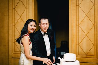 bride-in-a-white-qipao-with-gold-embroidery-and-red-trim-cuts-cake-with-groom-in-black-tuxedo