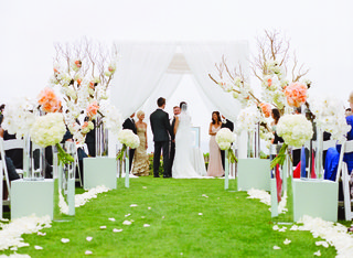 peach-flowers-and-branches-at-beach-ceremony-with-white-canopy