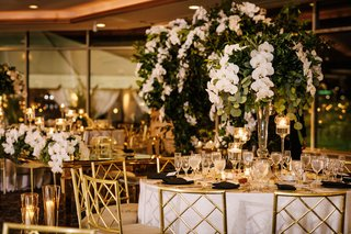 wedding-reception-round-table-gold-chairs-white-orchid-greenery-centerpiece-ballroom-reception