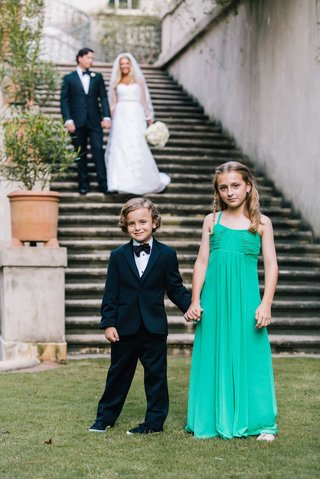 ring-bearer-in-black-tuxedo-and-bow-tie-with-flower-girl-in-long-green-tank-dress-braid