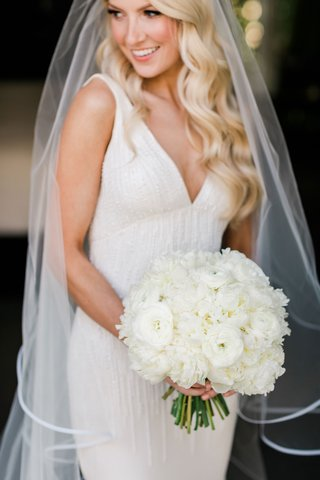 bride-with-long-blonde-hair-holding-white-bouquet-ranunculus-peony-flowers-green-stems